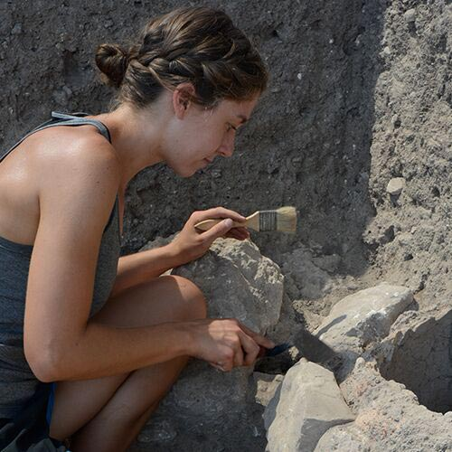 A young woman crouching down is using a trowel and brush to remove dirt and rock at an excavation site